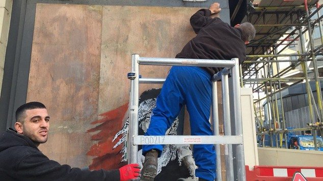 A new artwork by Banksy, depicting the girl from Les Misrables affected by tear gas, is being taken down by workmen
